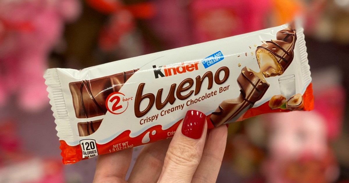 woman with red nails holding a Kinder Bueno candy bar