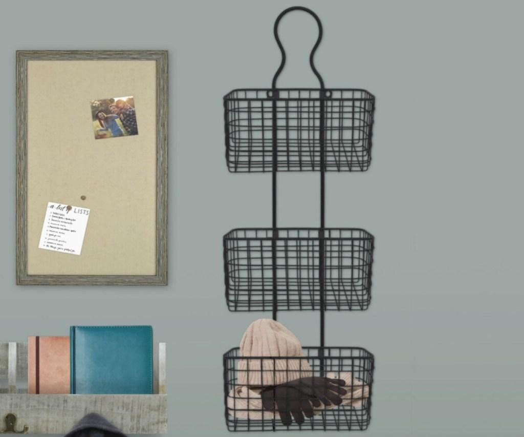 Three tier wire basket decor on wall near cork board