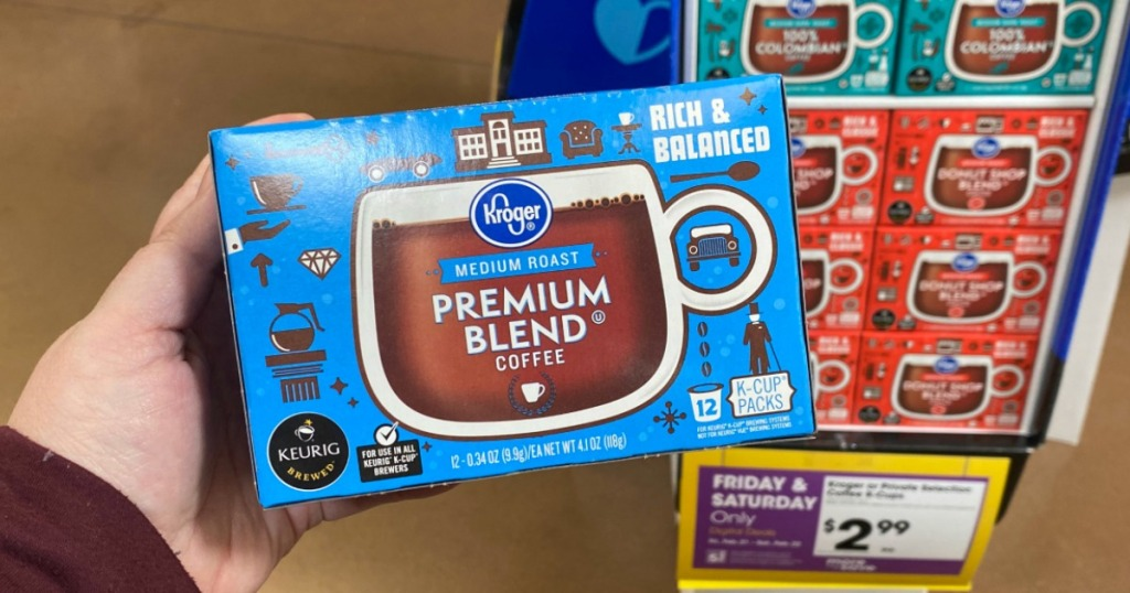 woman holding a box of Kroger K-Cups