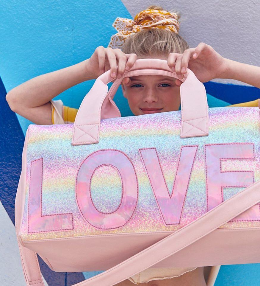 Girl holding up LOVE Duffel bag