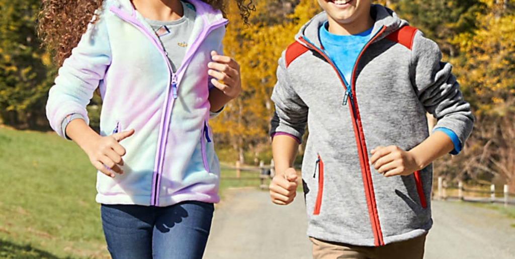 Boy and girl running and wearing sweaters, outdoors