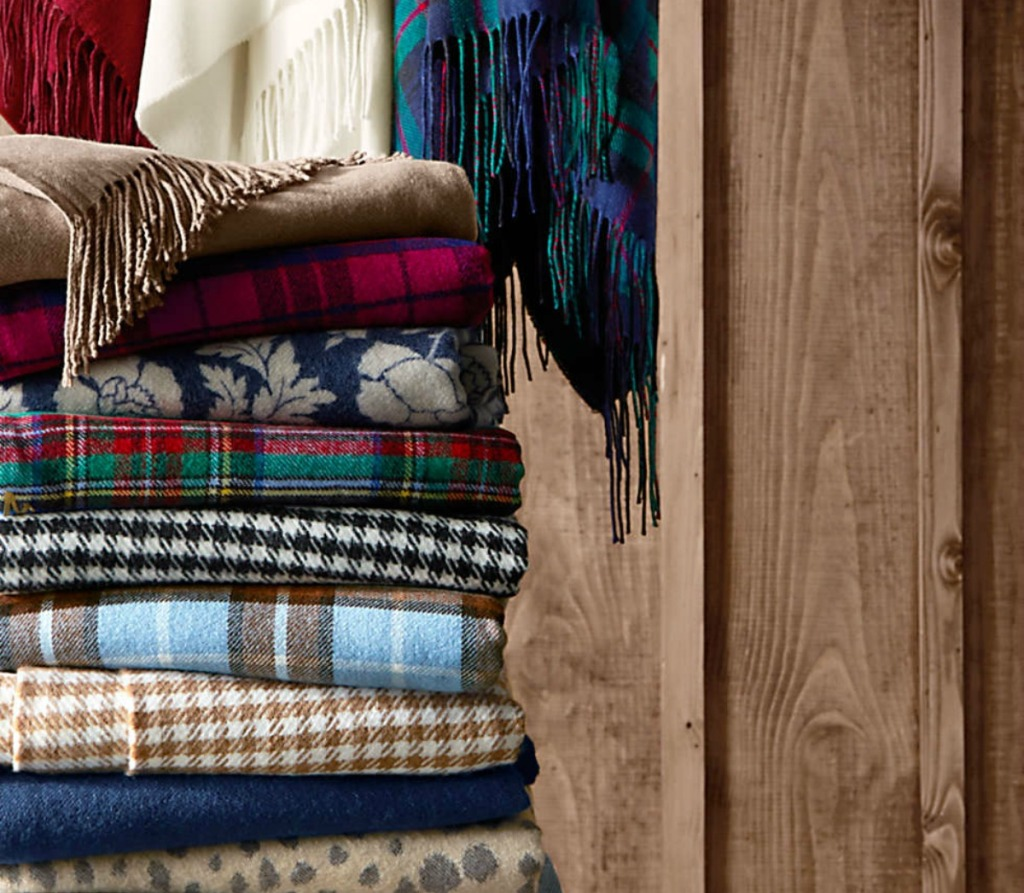 stack of various folded Lands' End printed throw blankets