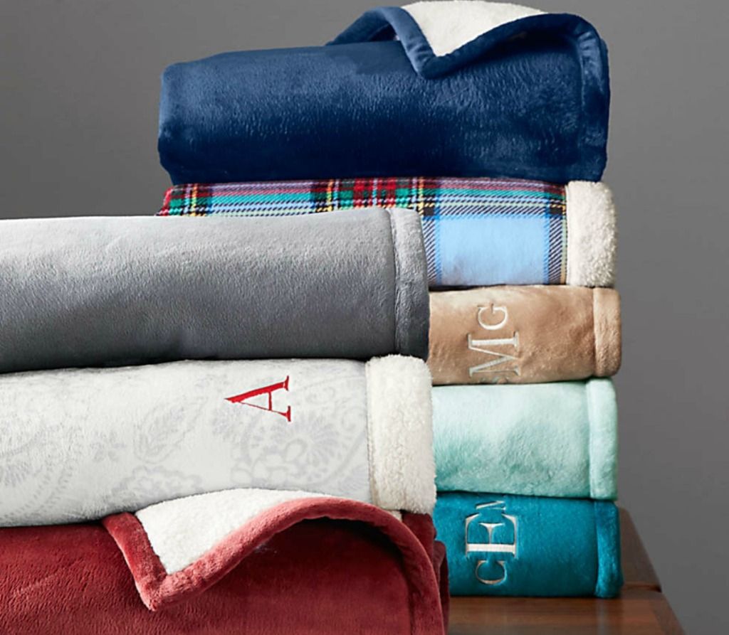 stack of sherpa throw blankets in various colors