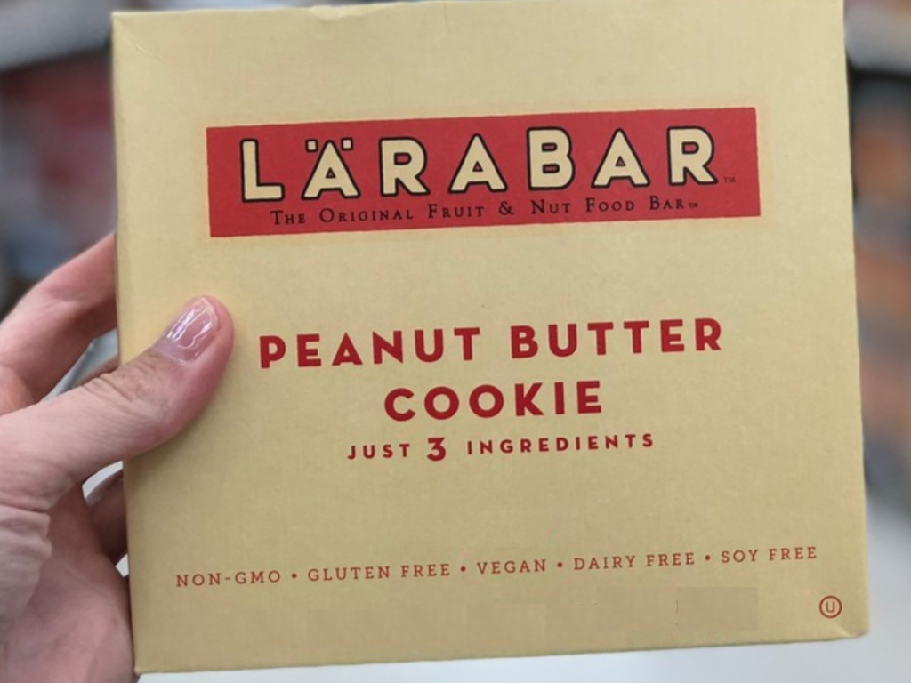 Hand holding box of peanut butter protein bars