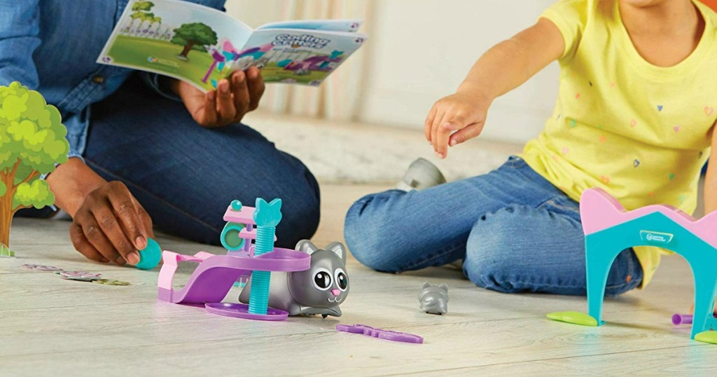 two people playing with a toy a animal and playset