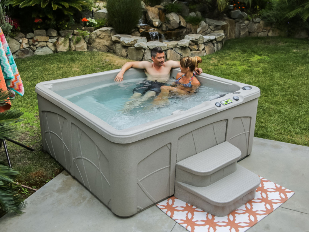 couple relaxing in hot tub in scenic back yard