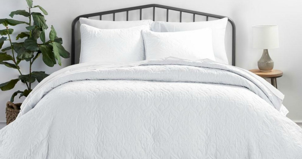 bed with pillows and white quilt