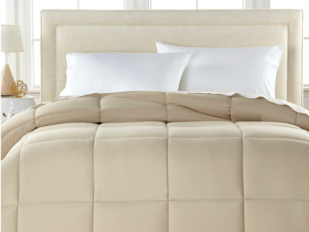 Tan comforter on made bed with white standard pillows