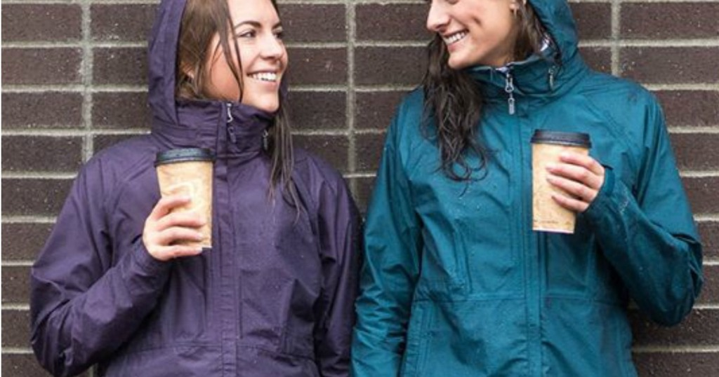 two ladies wearing rain jackets and drinking coffee