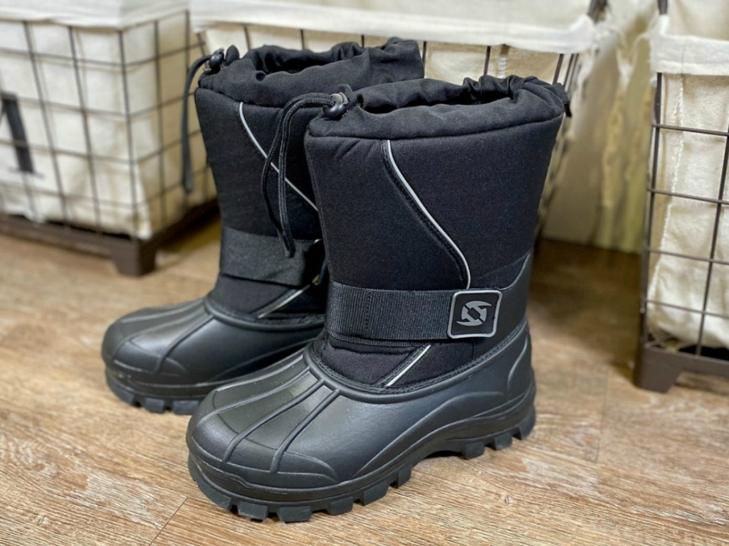 Pair of men's winter boots in entry way near baskets