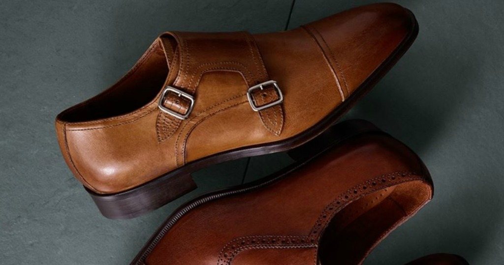 Cognac colored men's leather dress shoes in two styles on cement-style surface