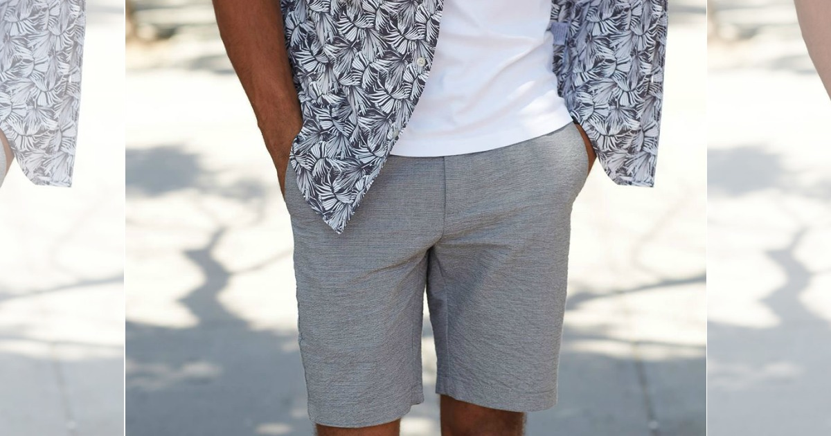 man wearing gray shorts and a white tee