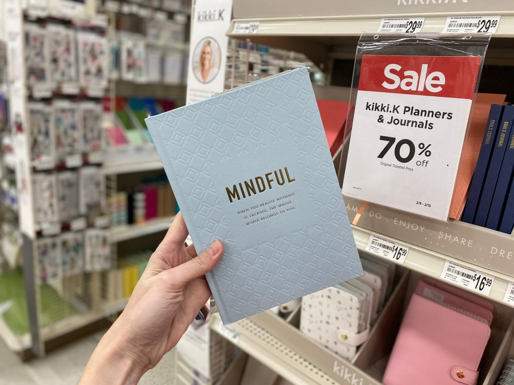 woman's hand holding up a Mindful Journal in store