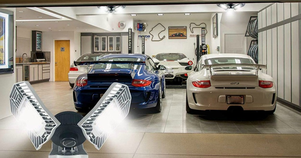 two sports cars in a garage with a light fixture superimposed on top