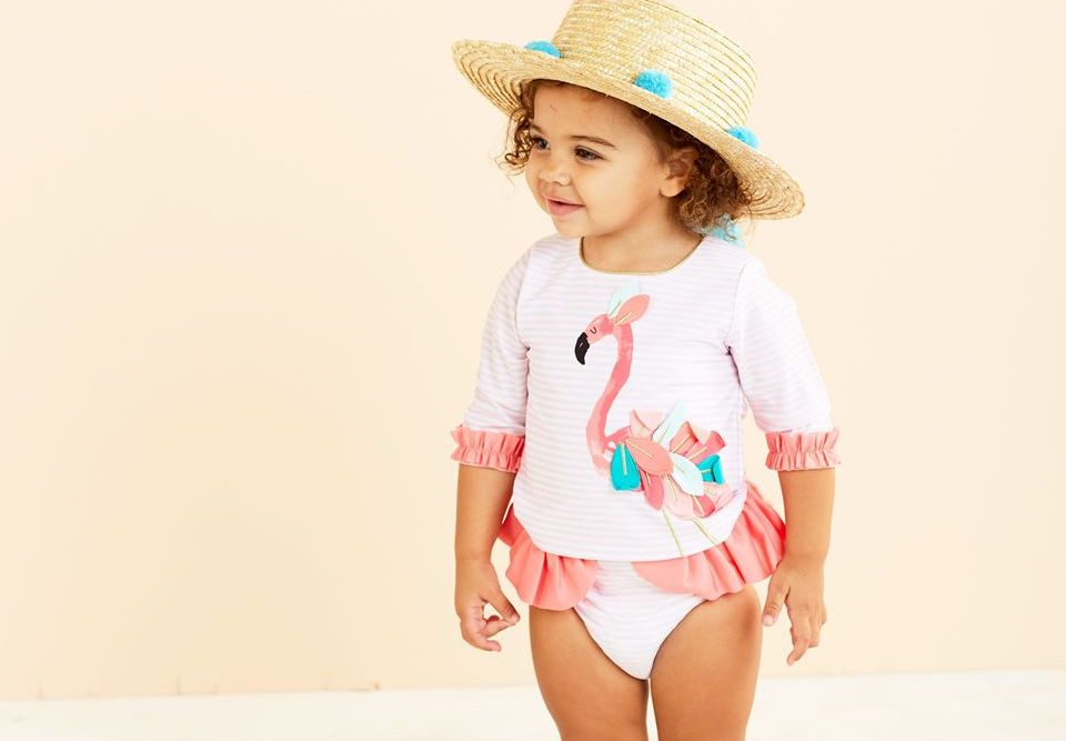 girl wearing a sun hat and a swimsuit with a flamingo on it