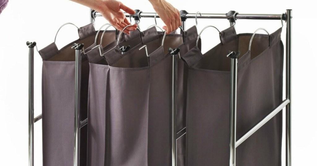 woman picking up hamper out of Neatfreak Laundry Sorter