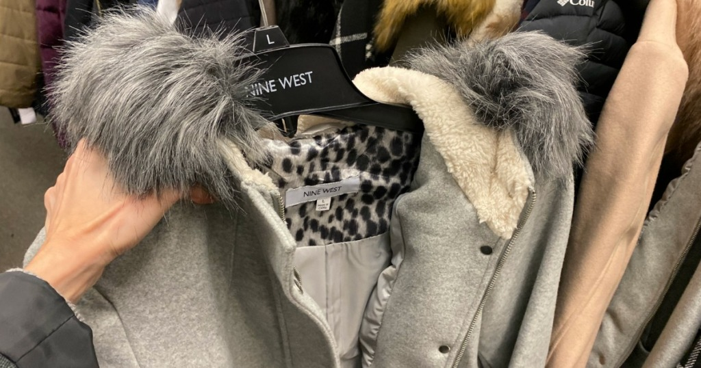 hand holding a grey jacket on a hanger