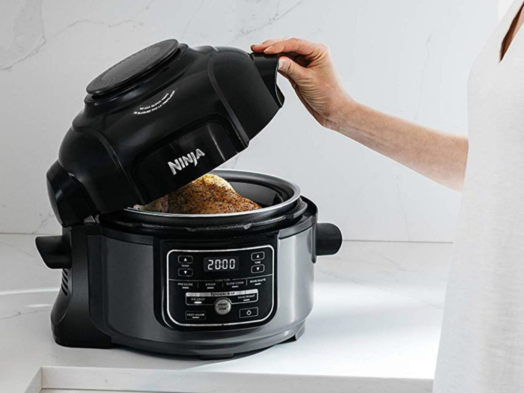 Woman opening a black and silver pressure cooker