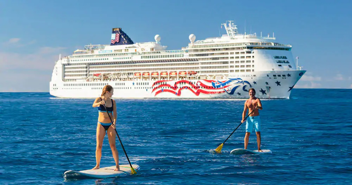 Norwegian cruise ship with paddleboarders in foreground