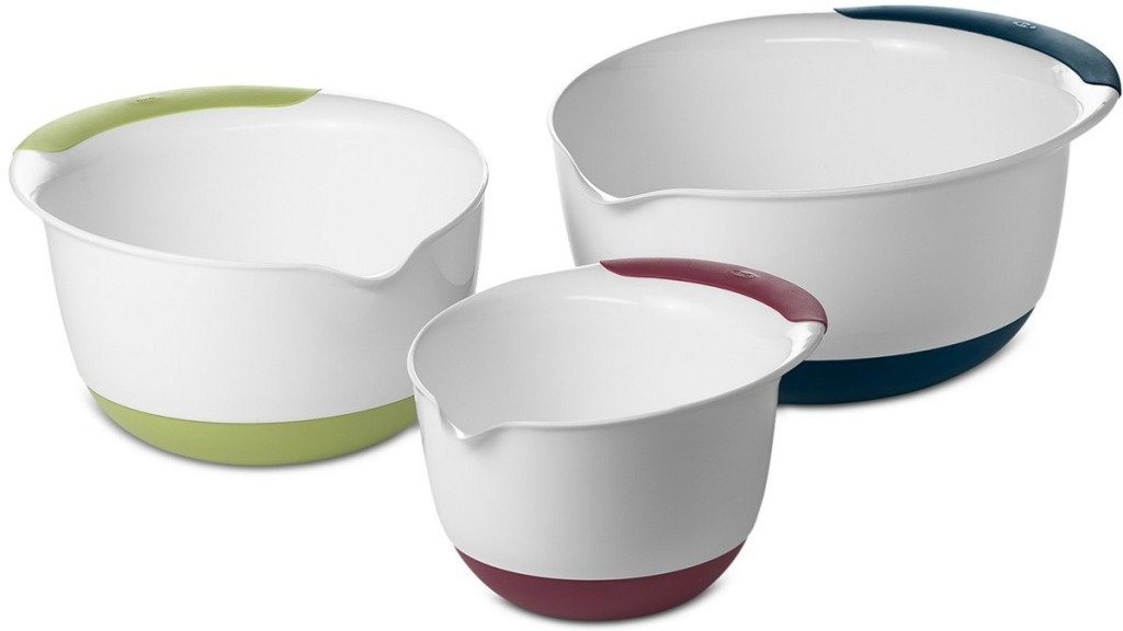 Three white mixing bowls with colored rims on white background