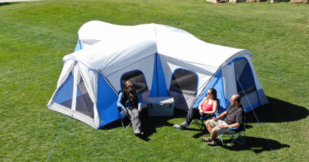 people sitting outside large tent on grass
