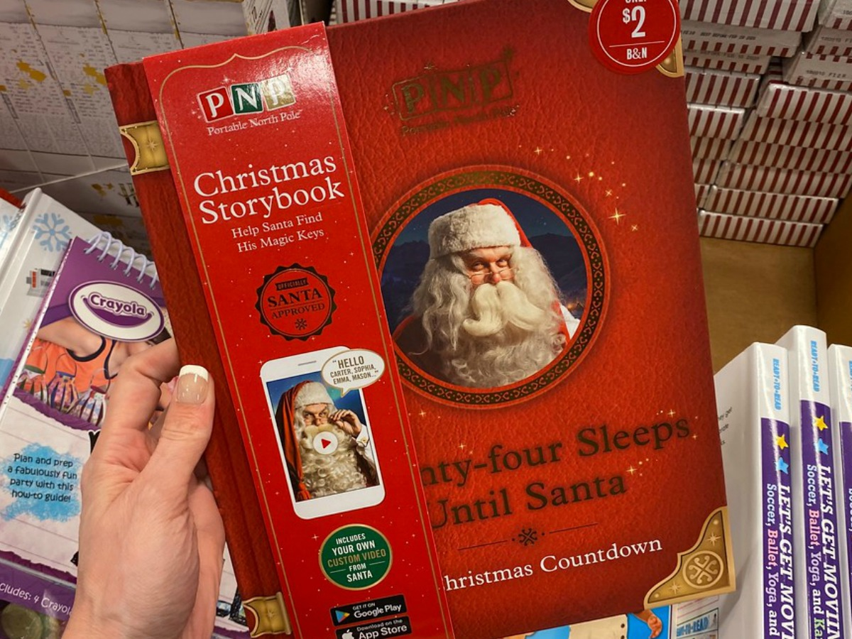 hand holding red Christmas book with Santa on it