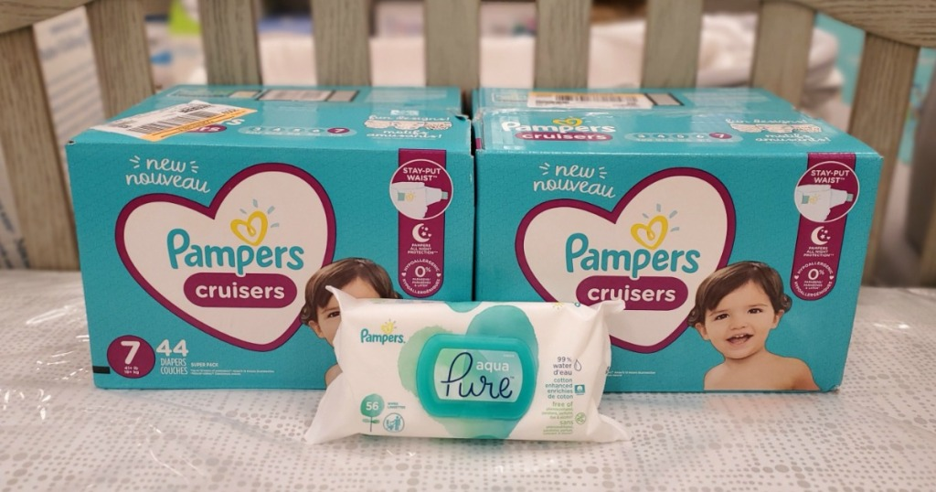 two boxes of Pampers diapers and a small package of wipes in front of them