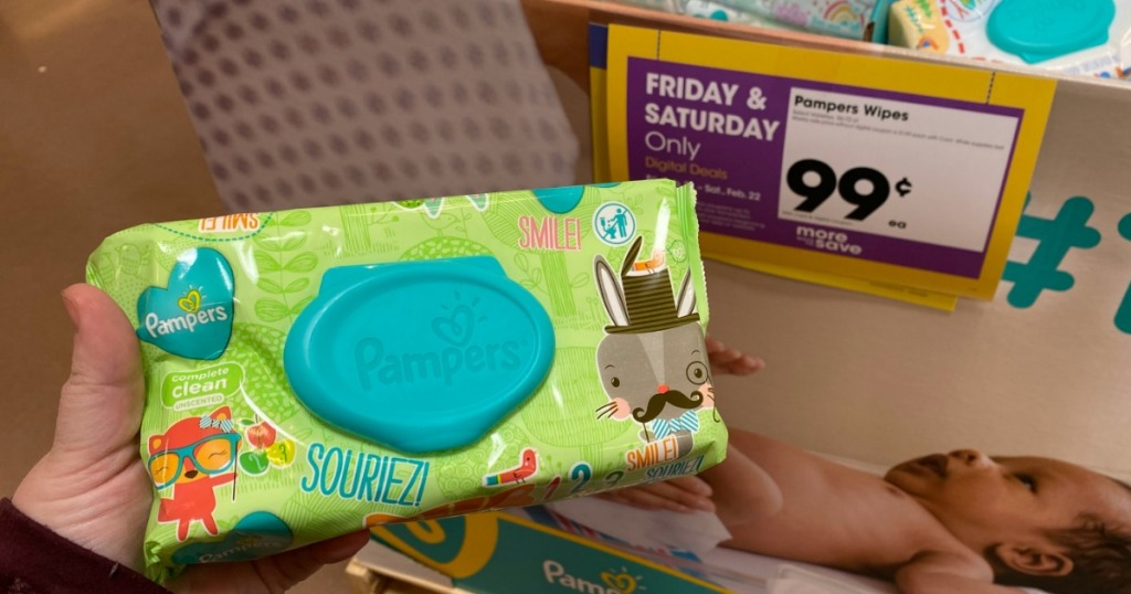woman holding Pampers wipes pack in front of a sale sign