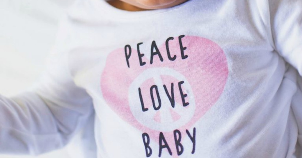 "Baby wearing a white bodysuit that says ""peace love baby"""