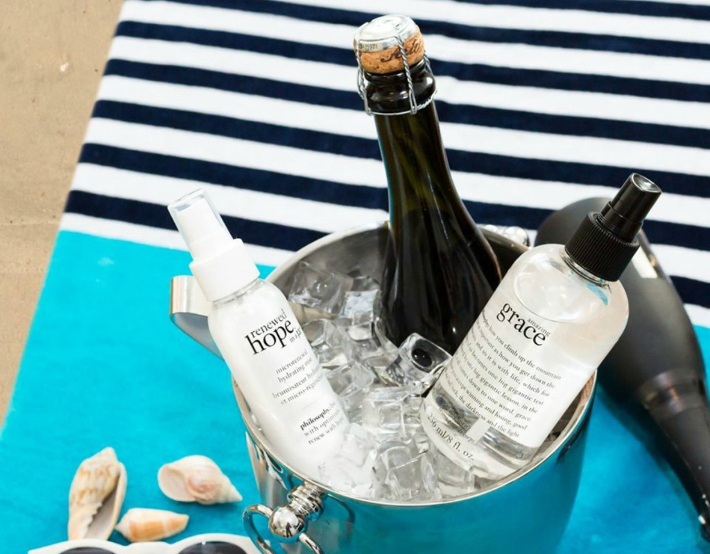 Philosophy perfumed body spritz in a bucket with champagne, ice and another Philosophy skin care product