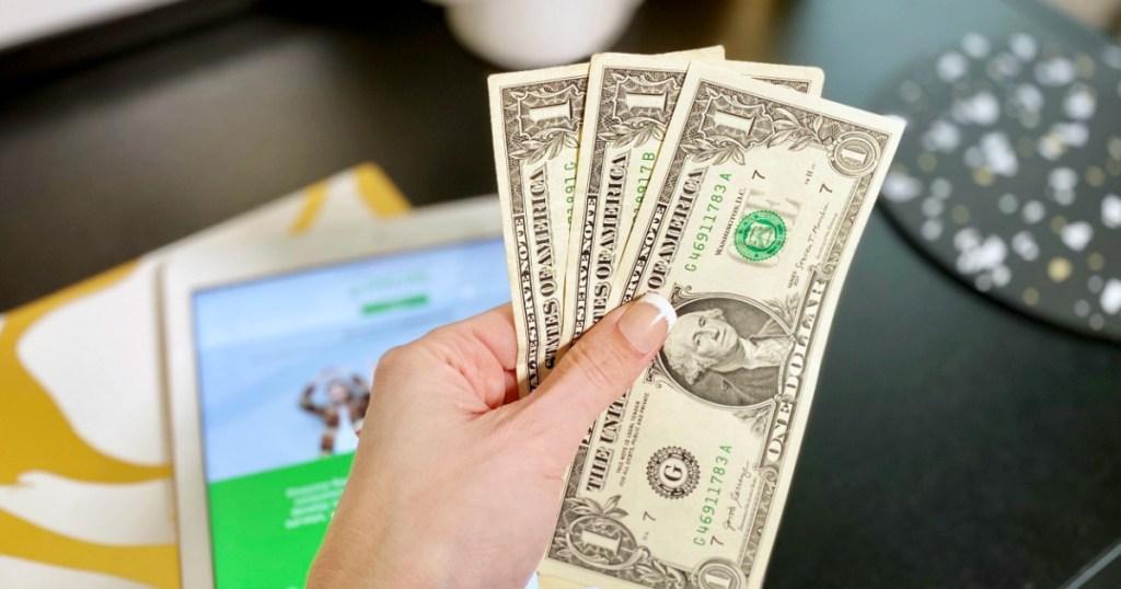 hand holding three dollar bills