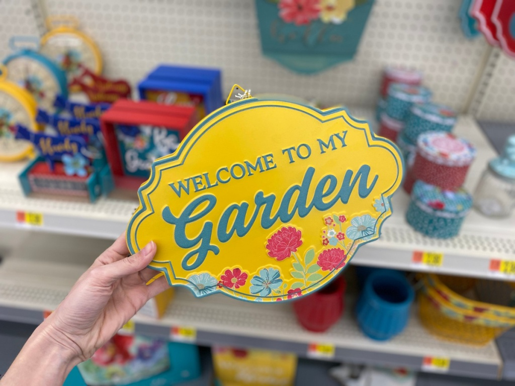hand holding yellow welcome to my garden sign
