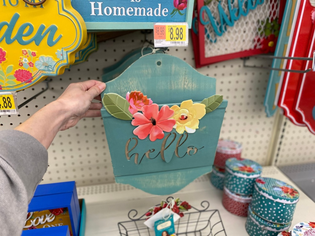 hand holding teal hello sign with pink and yellow flowers