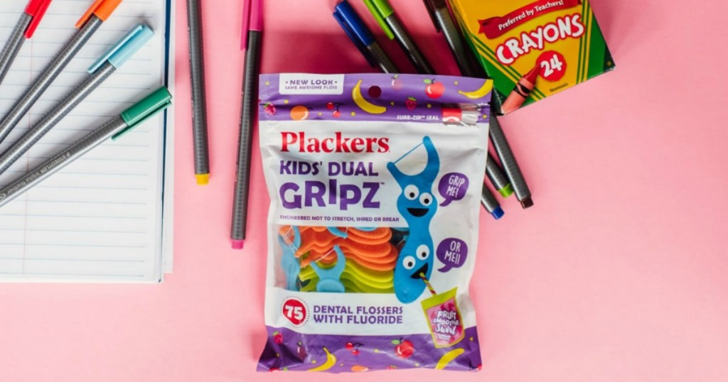 Plackers kids floss picks bag surrounded by crayons and markers on a pink background