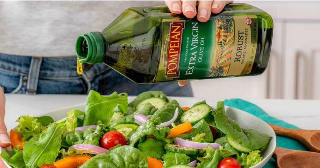 Person pouring Pompeian Olive Oil over salad