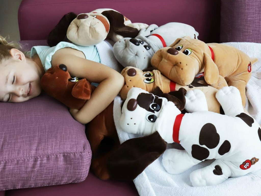 Young girl laying on sofa with a ton of classic sized Pound puppies plush