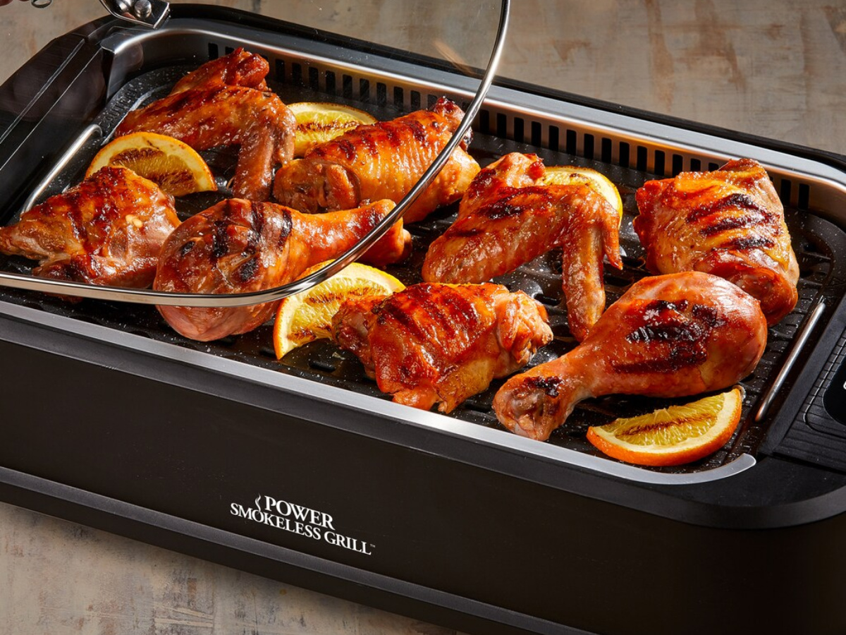 power smokeless black grill with chicken legs and orange slices in grill
