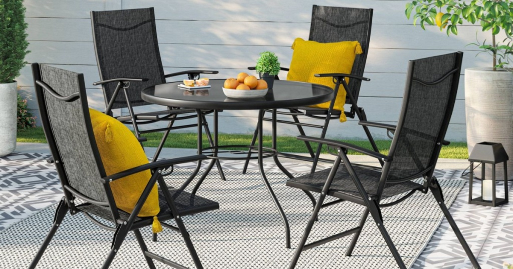 patio table and four chairs with yellow pillows and oranges on table
