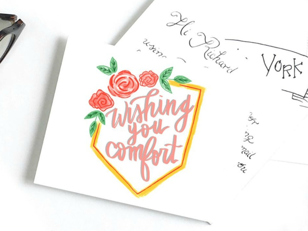Sympathy card with hand written style design on desktop near glasses