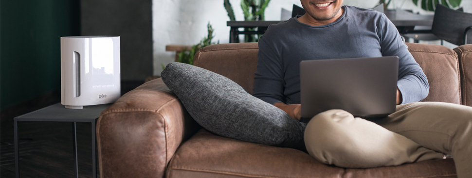 man sitting on couch with air purifier on table next to him