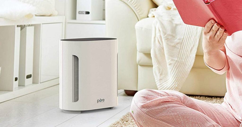 Pure Enrichment Air Purifier on floor next to a woman reading a book