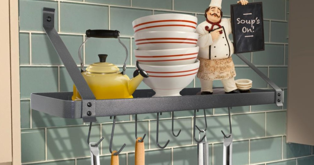 storage pot rack with bowls and a kettle on shelf and utensils hanging off of it