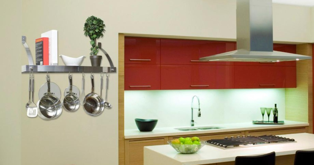 stainless steel pot rack with pans and utensils stored above and hanging off in kitchen