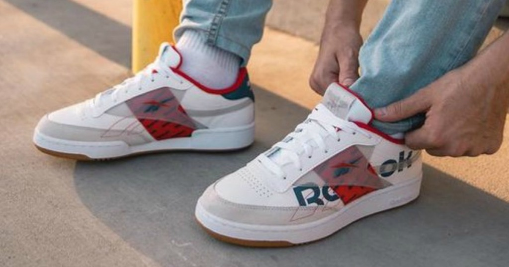 person tucking their pants behind tongue of Reebok shoes