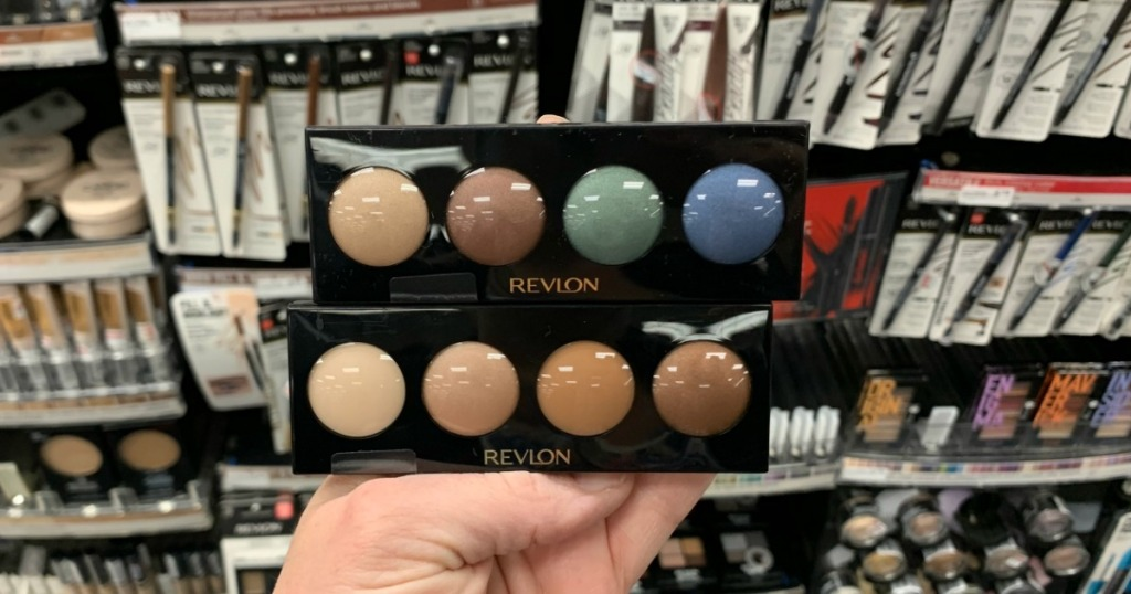 Hand holding eyeshadow in front of shelf