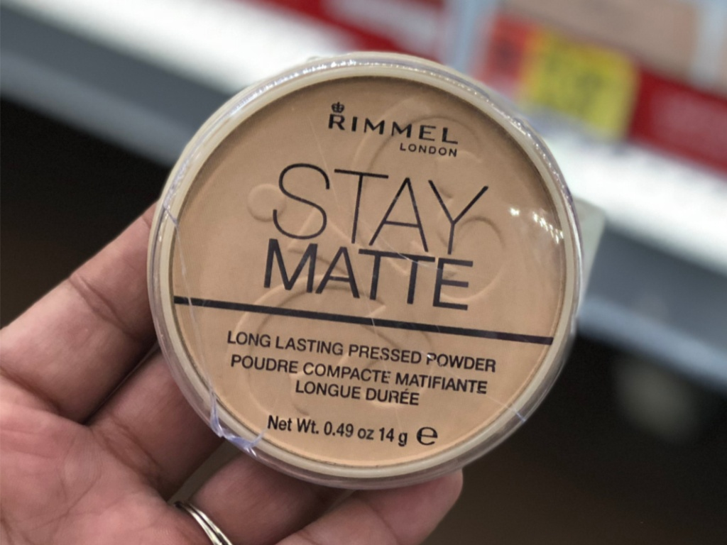 Man's hand holding makeup in store aisle