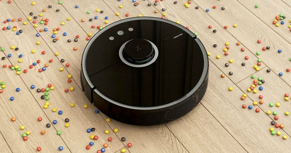 Robotic vacuum cleaning up a large mess of small colorful snacks on hardwood flooring