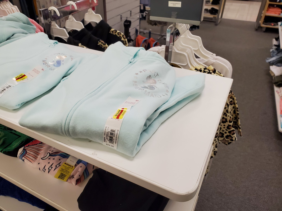light blue zip up hoodies folded in-store