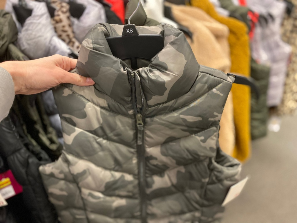 hand holding camo puffer vest in store
