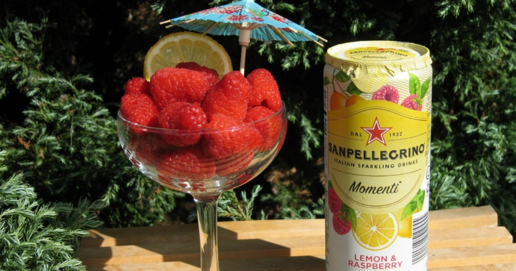 Sanpellegrino Momenti can next to glass full of raspberries
